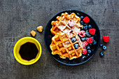Homemade Belgian soft waffles with berry on black plate, espresso cup and cubes of brown sugar