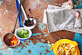Verschiedene Gemüse in Suppenkellen, daneben Kürbis und Knoblauch