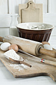 Various baking utensils, flour, eggs and milk on a wooden chopping board
