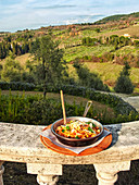 Ein Teller mit Pasta vor toskanischer Landschaft (Italien)