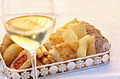 Bread and pastries on a tray in front of a glass of white wine