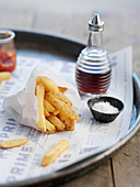 French fries in a paper bag, with a small bowl of salt