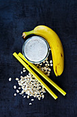 A banana smoothie in a glass next to oats, straws and a banana