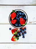 Blueberries and strawberries in a bowl and on a wooden surface (seen from above)