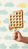 A child holding a yoghurt waffle on a stick with a bite taken out
