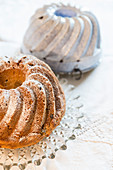 A Bundt cake and a baking tin with icing sugar