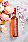 A bottle of rosé wine with condensation, straws and glasses next to a bunch of buttercups