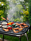 Prawns and vegetable kebabs on a grill