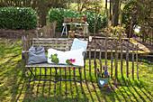 Gartenbank mit Kissen vor Staketenzaun