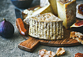 Cheese platter with cheese assortment, figs, honey, freshly baked bread and nuts on wooden board over grey concrete background