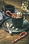 Wintergetränk: Heiße Schokolade im Becher mit Marshmallows und Zuckerstange