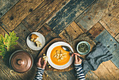 Flat-lay of female hands and Fall warming pumpkin cream soup with croutons and seeds over rustic wooden table