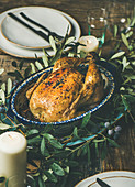 Whole roasted chicken in tray for Christmas eve celebration decorated with olive tree branch, plates, glasses and candles over rustic wooden background