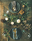 Christmas or New Years eve holiday table setting: Flat-lay of plates, silverware, glassware, candles, olive branches and toy festive decorations