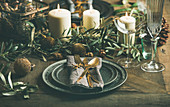 Christmas or New Years eve holiday table setting: Plates, silverware, glassware, candles, olive branches and toy festive decorations