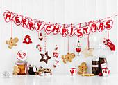 Merry Christmas Schriftzug mit Weihnachtsdeko, Lebkuchenfiguren und eingemachten Geschenken