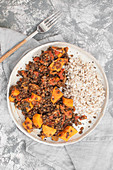 Black lentils with sweet potatoes, tomatoes and kale, served with pearls barley (Vegan dish)
