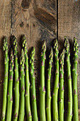 Green asparagus spears on a wooden background (top view)
