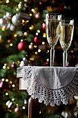 Champagne flutes on a table, with a Christmas tree behind