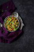 Indian vegetable curry in a bowl on a dark background (top view)