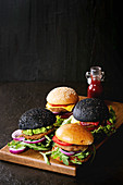 Homemade burgers in black and white buns with avocado, tomato sauce, lettuce, arugula, cheese, onion