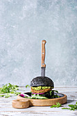 Homemade burger in black bun with avocado, arugula, onion on wood serving board