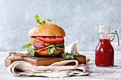 Homemade burger in classic bun with tomato sauce, arugula, meat, cheese, onion, bottle of ketchup on wood serving board