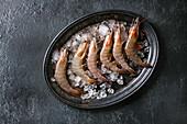 Fische rohe Garnelen mit Eis auf Vintage-Metallplatte (Aufsicht)