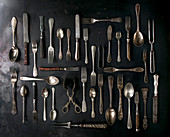 Big set of vintage cutlery over black metal background