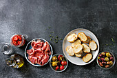 Ingredients for making tapas or bruschetta: Crusty bread, ham prosciutto, sun dried tomatoes, olive oil, olives, pepper, greens on plates over dark texture background
