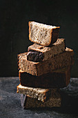 Variety loaves of sliced homemade rye bread whole grain and seeds in stack over old dark background