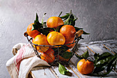 Ripe organic clementines or tangerines with leaves in basket standing with kitchen towel