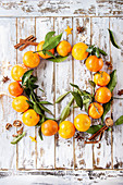 Clementines tangerines with leaves as Christmas wreath with cinnamon sticks and anise over white wooden plank background