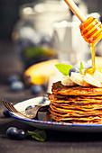 Honig fliesst von Honiglöffel auf einen Stapel Pfannkuchen (Nahaufnahme)