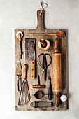 Top view of a group of vintage cooking utensils on a wood cutting board