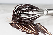 A whisk with chocolate ganache (close up)
