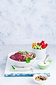 Rote-Bete-Hummus serviert mit Walnüssen und Gemüsesticks