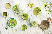 Matcha green vegan smoothie with chia seeds and fresh mint in glasses and bottles over marble background