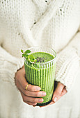 Matcha green vegan smoothie with chia seeds and mint in glass in hands of female wearing white sweater