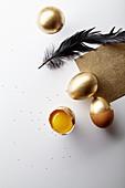 Osterdeko: Golden gefärbte Hühnereier, schwarze Feder und Goldpapier
