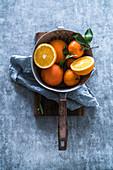 Fresh oranges in a metal colander (top view)