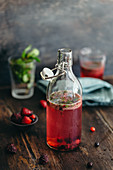 A refreshing drink with wild berries and mint in a glass bottle