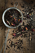 Tea leaf mixture with rose petals and white cornflowers in a sieve