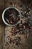 Teeblättermischung mit Rosenblüten und weissen Kornblüten in Sieb