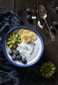 Smoothie-Bowl mit Sojajoghurt, Früchten, Mohn und Kokosflocken