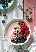 A smoothie bowl with raspberry yoghurt, fresh berries and seeds