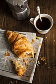 A croissant on newspaper, a coffee pot, and a cup of coffee