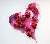 Frozen raspberries on a hand painted pink watercolour heart