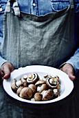 Mann mit Schürze hält Teller mit frischen Champignons in den Händen
