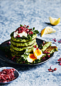 Healthy eating, glutin free green pea pancake stack with goat cheese, egg, watercrese and mint greens and a side of lightly reduced balsamic red onions
